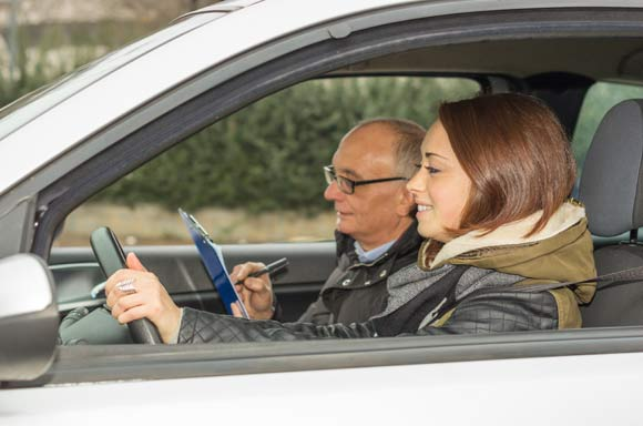 Girl rides during his driving test - caucasian people - Lifestyle and driving school concept